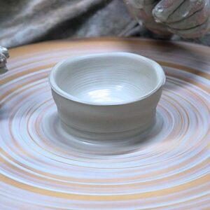 spinning clay on pottery wheel