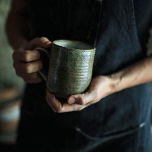 man holding ceramic mug